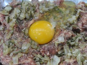 adding the egg and sauteed onion and herbs